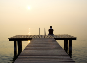 man sits at end of dock as he contemplates finding the best rehab center for alcoholism to address his alcohol abuse issues