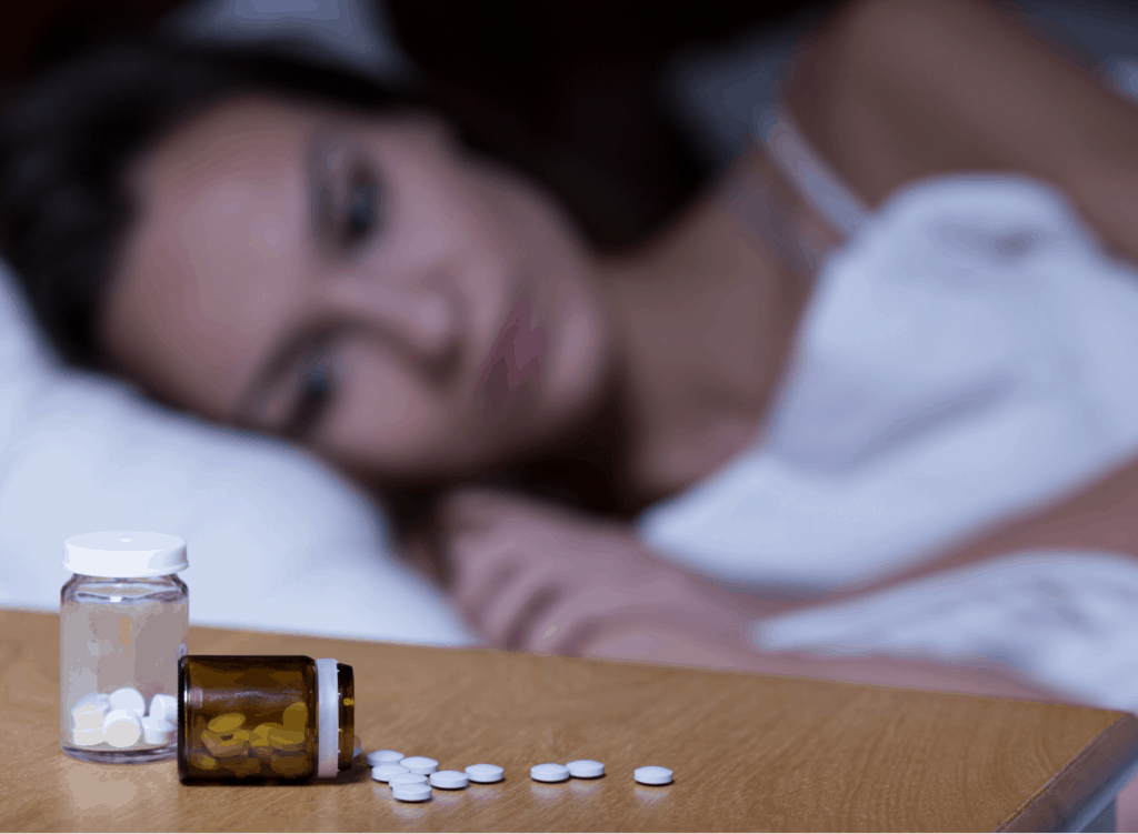 woman laying in bed next to a bottle of sleeping pills as she battles a sleeping pill addiction