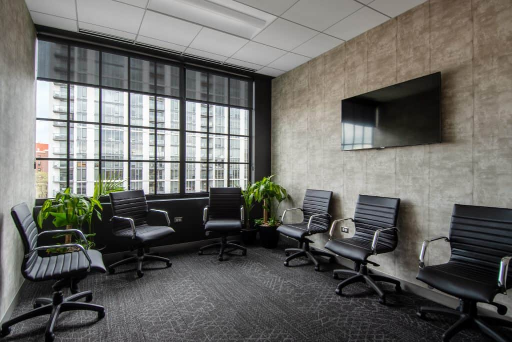 The spacious virtual & group therapy room at CRC's rehab center in Chicago featuring modern warm decor, greenery, neutral ombre sponge painted walls and big windows overlooking the city of Chicago.