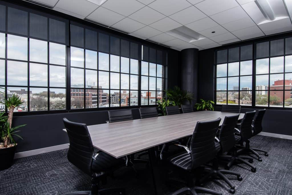 The meeting room at CRC's rehab center in Chicago featuring a long, modern, neutral table with black chairs, warm decor, greenery, dark ombre sponge painted walls and big windows overlooking the city of Chicago.