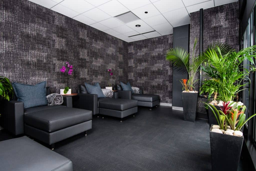 The spacious, modern IV therapy lounge in CRC's rehab center in Chicago which has big, gray chaise lounges, beautiful gray modern wallpaper, and gorgeous plants.