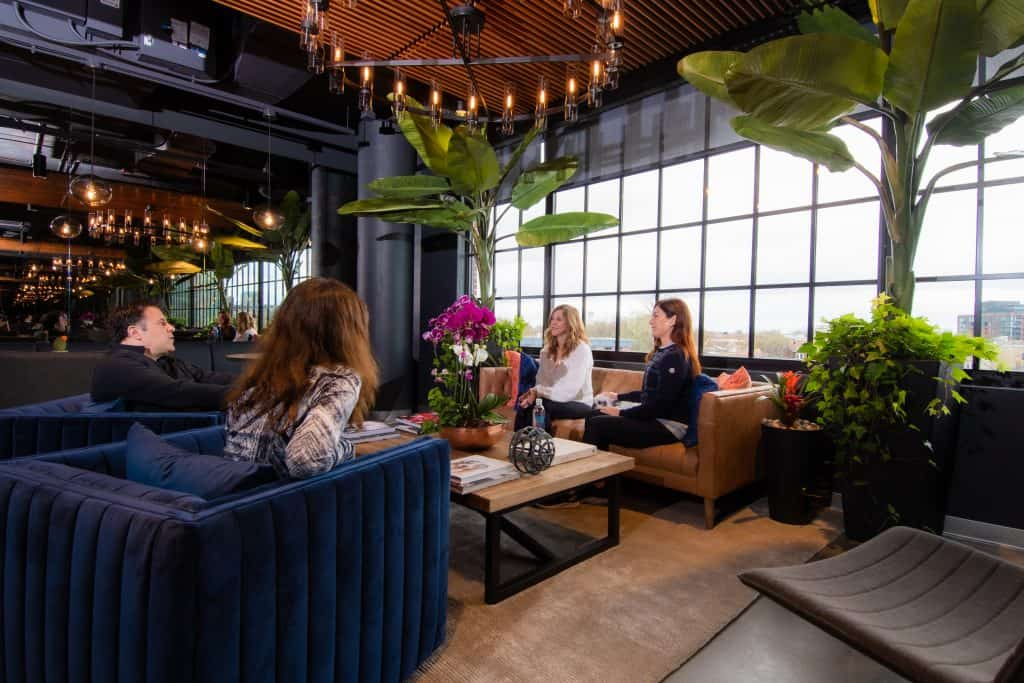 The lobby seating at CRC's rehab center in Chicago featuring rehab patients socializing while sitting on big blue chairs, and a copper couch, surrounded by modern decor and lots of greenery.