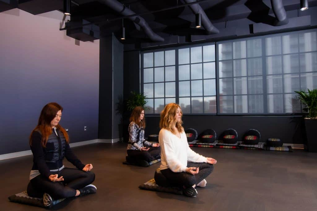 Female rehab patients at CRC's rehab center in Chicago participating in meditation in the meditation room which features dim lighting, warm tones and a big window that looks out to the city of Chicago.