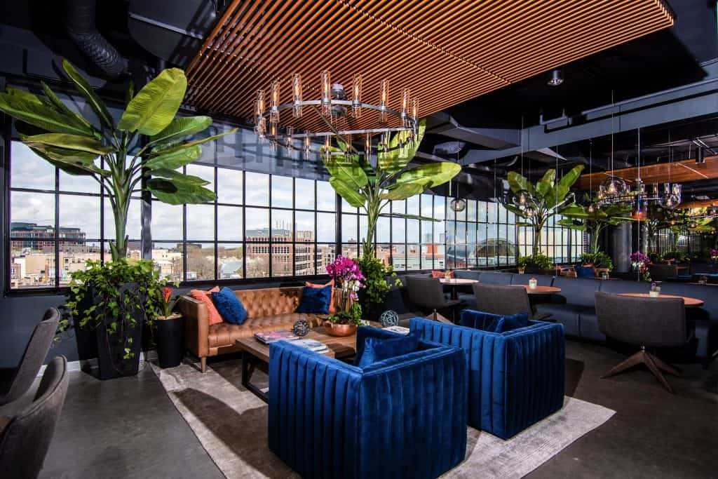 The open seating area at CRC's rehab center in Chicago featuring a modern decor, big blue chairs, copper furniture, and plenty of greenery.