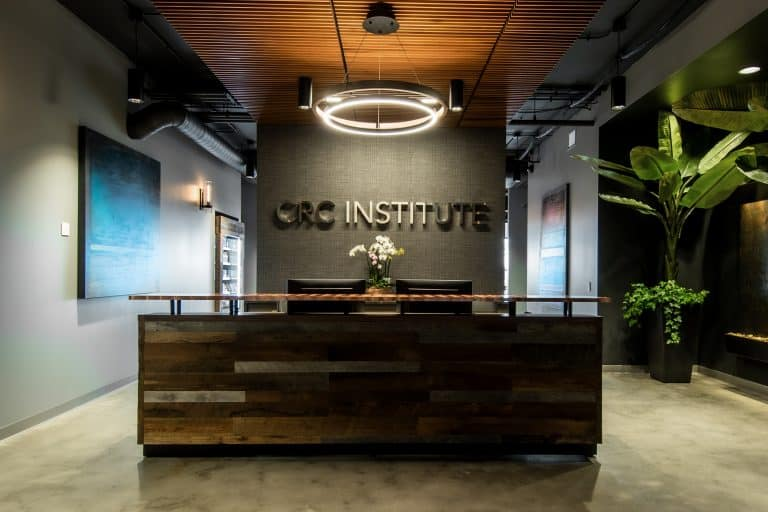 The front desk reception area at CRC Institute's rehab center in Chicago is modern and elegant with black and copper tones, a big chandelier, and the CRC Institute logo displayed on the wall behind the copper desk.