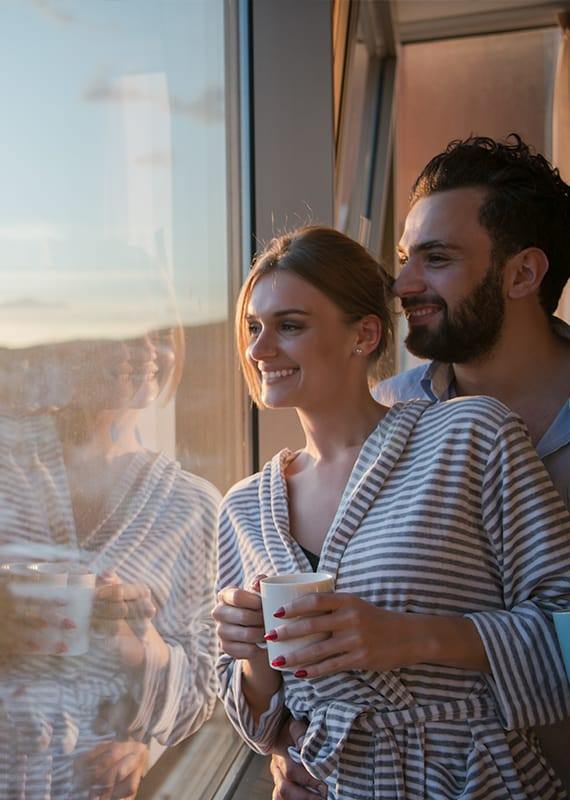 Man and women standing close to one another while drinking coffee and looking out the window to see the city of Chicago at CRC's rehab center in Chicago